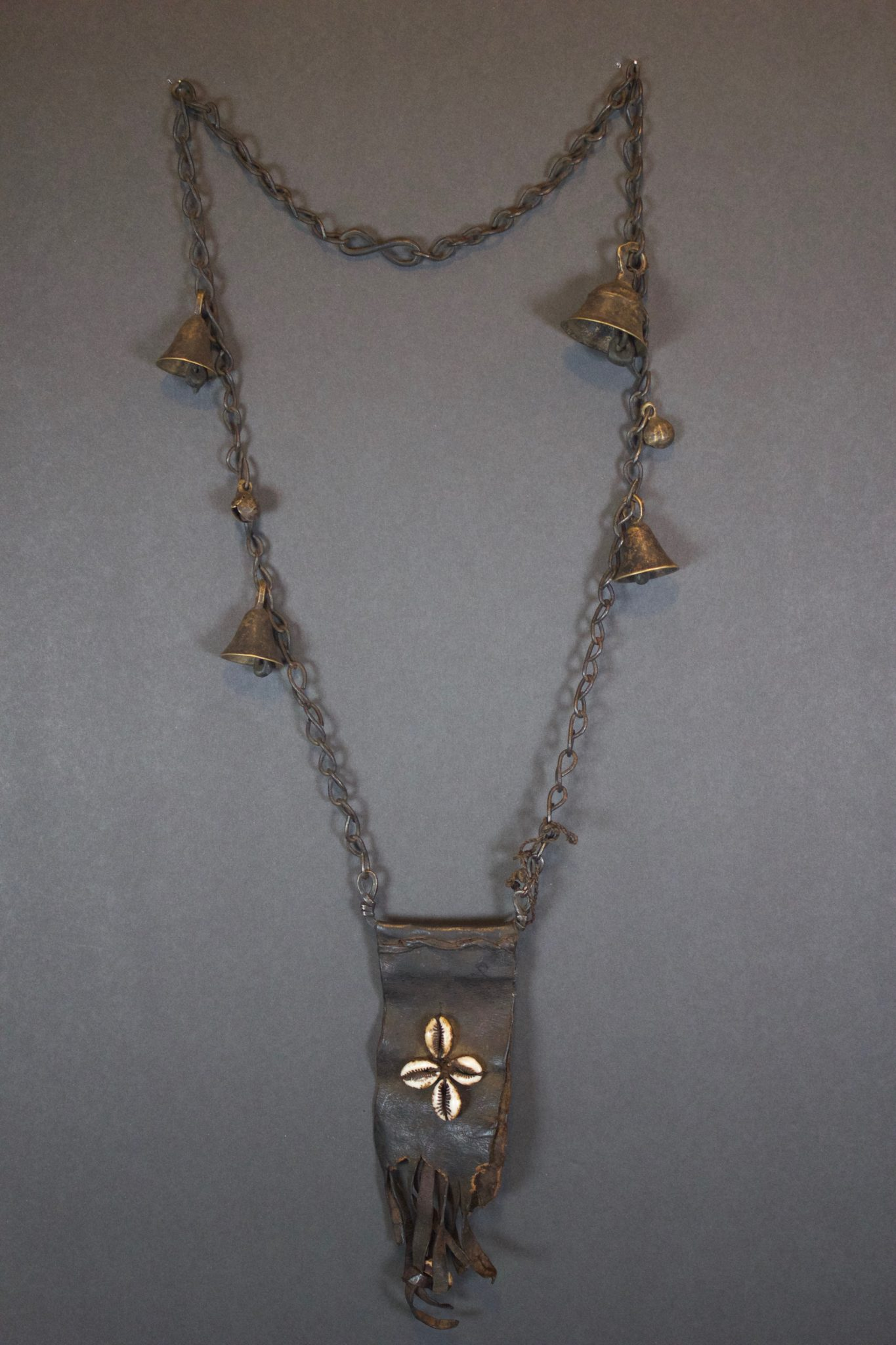 """Shaman Bell and Amulet Necklace, Nepal, Early 20th c.,Shaman Bell and Amulet Necklace, Nepal, Early 20th c., Leather Amulet with the four cowrie shells and brass conical bells on a chain, is a sacred ritual necklace is wornto facilitate entering a trance state. The bells make a nice sound when worn or hung in the wind. The sound represents a caravan of yaks coming down a mountain creating a magical link to their ancestors who migrated over the Himalayas from Tibet to Nepal, 28 ½"""" x 3 ¼"""" x 1"""", $295"""