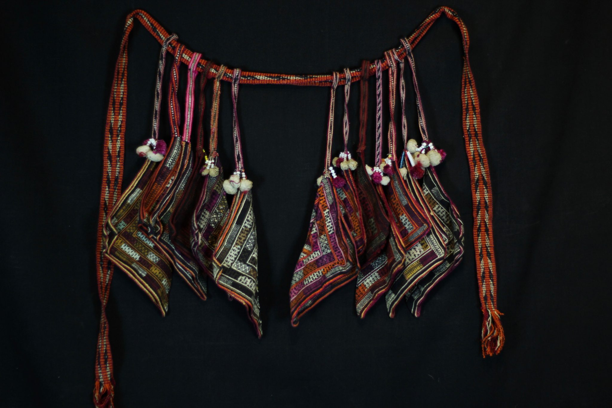 "Shamanic Belt with full set of 12 Handkerchiefs, Da Bac district, Hoa Binh province, Vietnam, Tight Trouser Dao people, Early to mid 20th c. Cotton, hand embroidered with silk. Worn by shaman while performing religious rituals. A complete belt would have a minimum of 12 handkerchiefs (embroidered squares). The belt is passed down through generations, revealing its history. If a shaman has two sons or apprentices, he will spit the belt and the new shaman's wife will make the other necessary handkerchiefs. 75"" x 18"" x 2 ½"", $775."