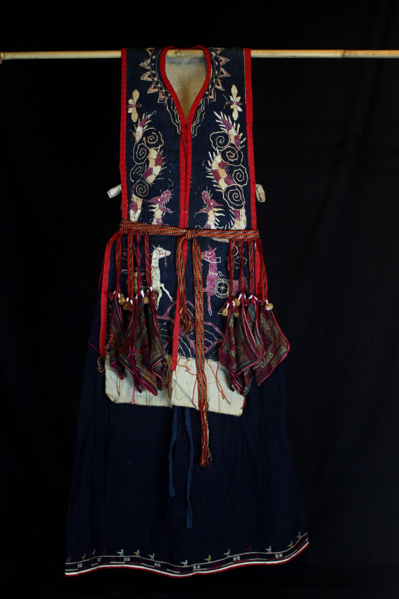 "Shaman's Costume Tunic and Belt, Vietnam, Yao people, Late 19th c, Cotton, indigo, silk embroidery, Worn only by high level shaman. The motif typically includes all the deities of heaven to clothe the shaman in the protection of the universe. Not a vain adornment, it is a reminder of man's place in the hierarchical order. Originally a female costume. Long ago shamans were women and men the providers. Not being encumbered by childbirth and rearing, men replaces women as shamans but retained this part of the sacred costume. *more information available. 47"" x 27 ½"" x 3"", $3100."
