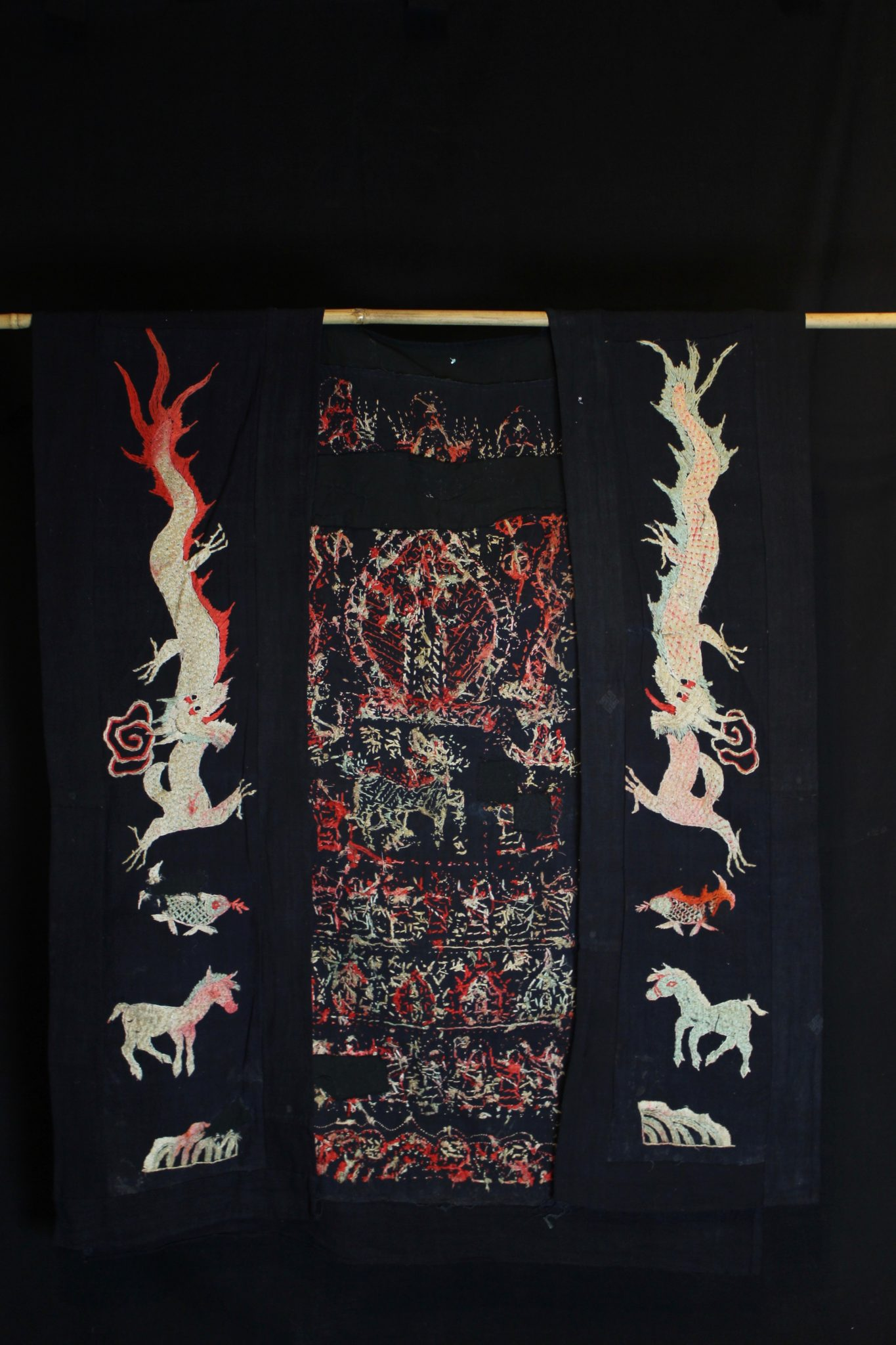"Dragon Robe/Ritual Cloak (back), Vietnam, Late 19th to early 20th c, Dao Lan-Tien people, Early 20th century, Cotton dyed with local indigo, hand embroidered with silk. Worn only by high level shaman. The use of expensive and difficult to obtain brighter European dyes indicates an exceptional piece. The motif typically includes all the deities of heaven to clothe the shaman in the protection of the universe. Not a vain adornment, it is a reminder of man's place in the hierarchical order. Originally a female costume. Long ago shamans were women and men the providers. Not being encumbered by childbirth and rearing, men replaces women as shamans but retained this part of the sacred costume. *more detailed information available. 45"" x 26"", $2900."