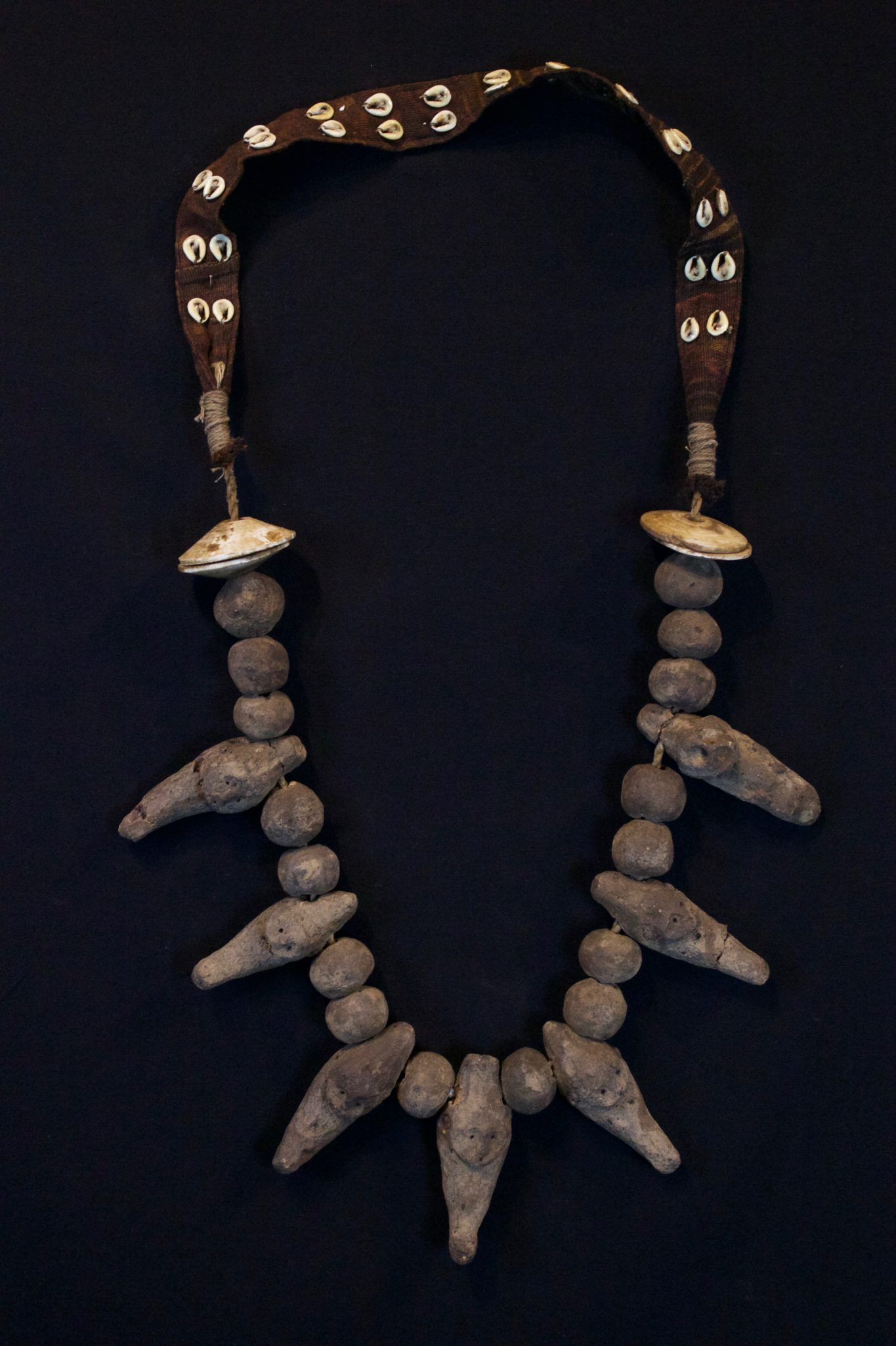 "Shaman Amulet Necklace, Timor Island, Lesser Sunda Islands, Indonesia, Early 20th c, Ceramic stone figures and beads, shell, cotton. Worn by the shaman for healing ceremonies. 21"" x 11"" x 1 ¾"" $650."