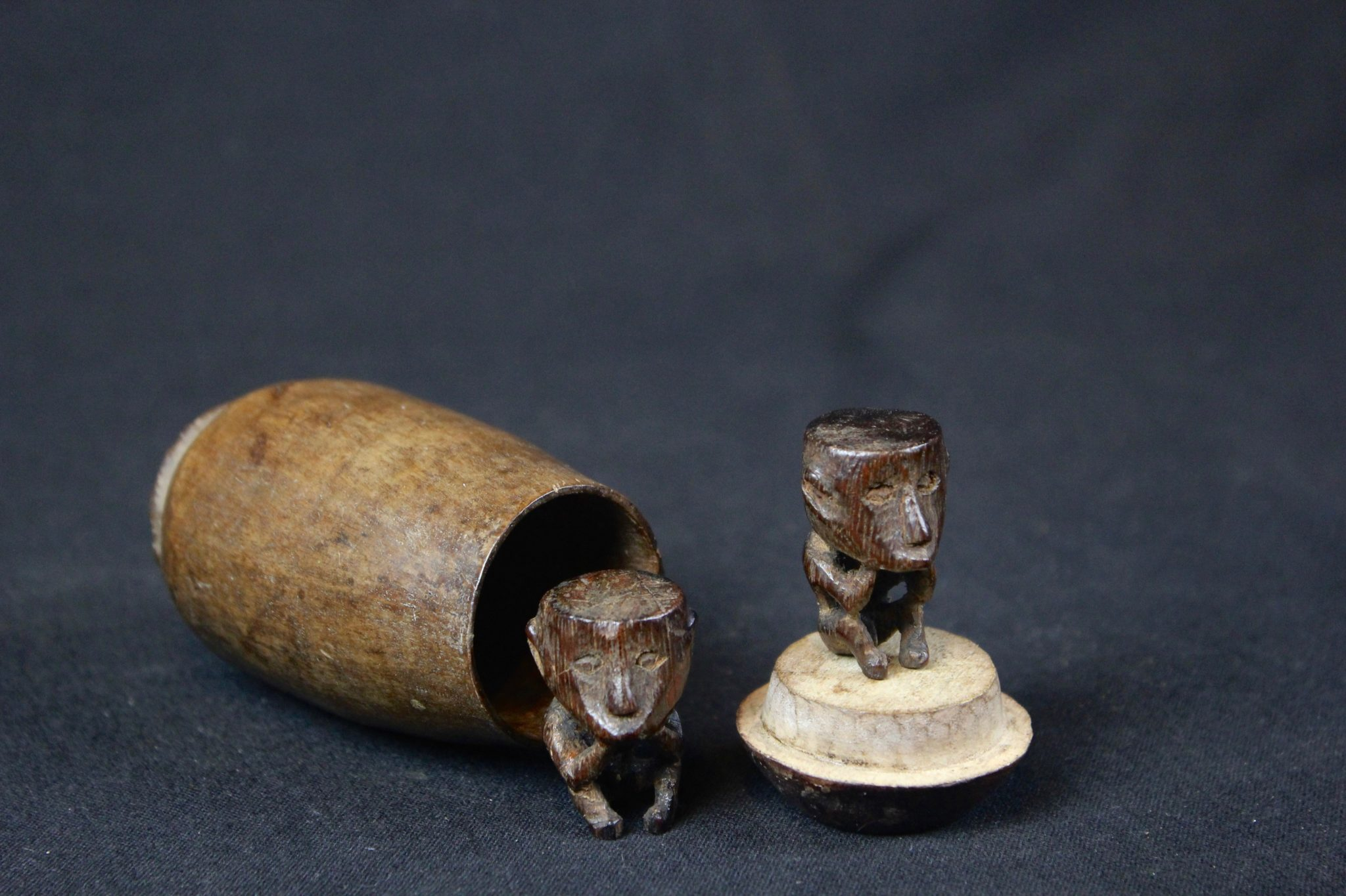 "Shaman Charms, West Sumba Island, Lesser Sunda Islands, Indonesia, Lamboya village, Early 20th c, Wood, smooth patina from use and age. Healing amulets. 3 ½"" x 2"" x 2"" (container); 1 ¼"" x ¾' x ½"" (each figure), $375."