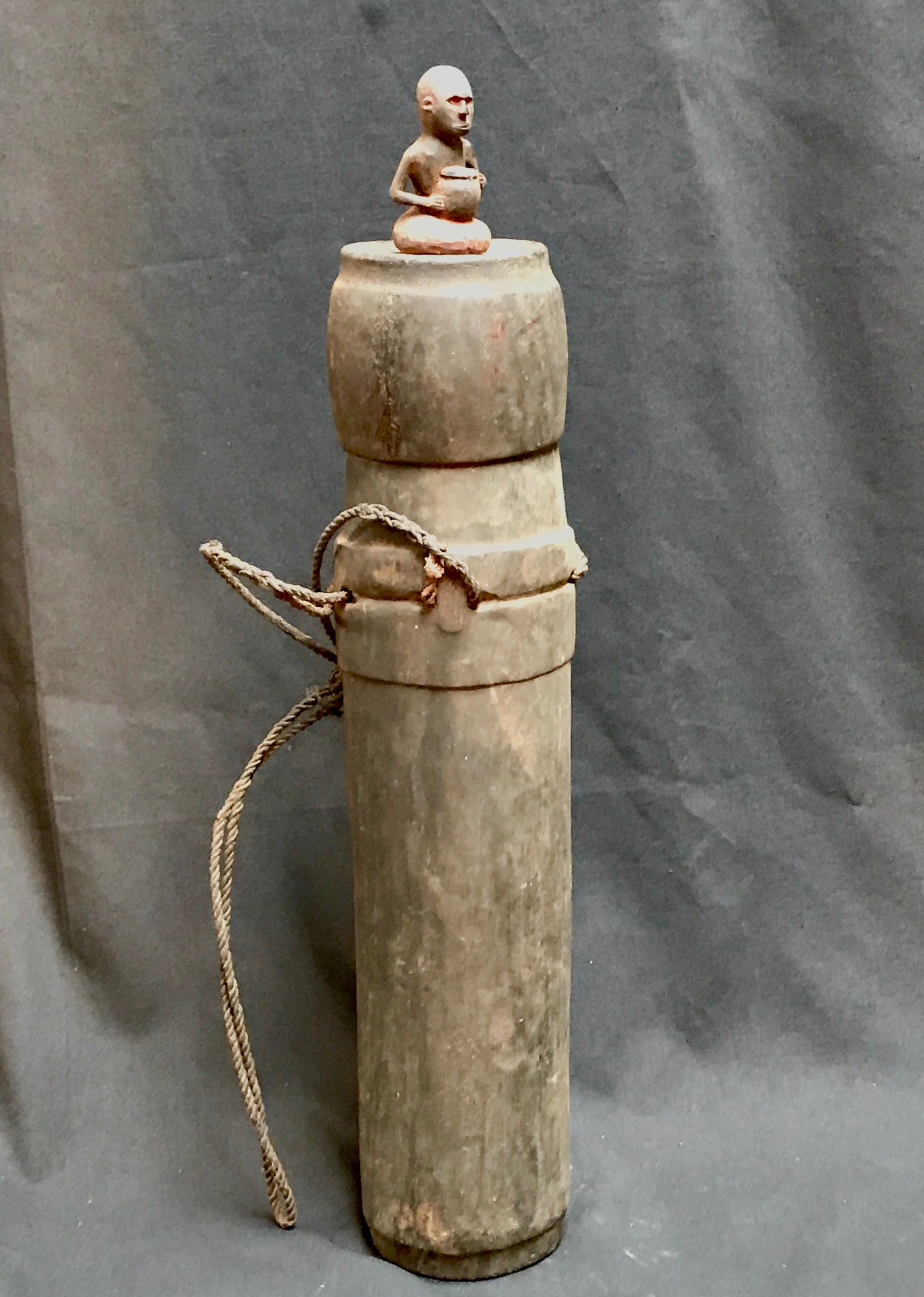 "Shaman's Medicine Jar/Container for healing herbs and substances, with carved seated figure holding a ceramic or wooden vessel. Sumba Indonesia, early 20th c., bamboo, wood, twine, pigment, 23"" x 7"""